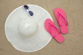 Infradito di colore rosa, occhiali da sole e cappello sulla spiaggia di sabbia — Foto Stock