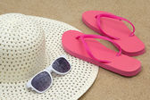 Picture of pink flip flops, sunglasses and hat on beach sand — Stock Photo