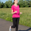 Slim woman running in park — Stock Photo