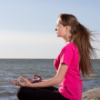 Girl in lotus pose sitting near sea — Stock Photo