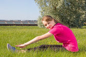 Young happy girl stretching in park — Stock Photo