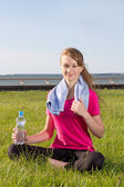 Woman sitting in park with towel and bottle — Stock Photo