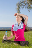 Tired woman sitting in park with towel and bottle — Stock Photo