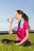 Tired woman drinking water after training — Fotografia Stock