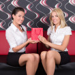 Young beautiful girls sitting on the sofa with present — Stock Photo