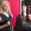 Hairdresser with hairdryer and smiling customer in beauty salon — Stock Photo
