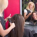 Hairdresser straightening woman's hair in beauty salon — Stock Photo #29056639