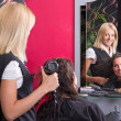 Young hairdresser with hairdryer and smiling customer in beauty — Stock Photo