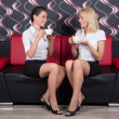 Beautiful female friends drinking coffee on the sofa — Stock Photo #29058239