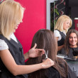 Female hairdresser makes hairstyle for beautiful girl — Stock Photo #29058859