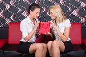Girls sitting on red sofa with gift — Stock Photo