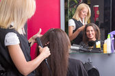 Hairdresser straightening woman's hair in beauty salon — Stock Photo