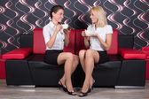 Beautiful female friends drinking coffee on the sofa — Stock Photo