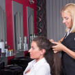 Постер, плакат: Young woman getting a new haircut by hairdresser at barbershop