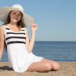 Woman in white dress and hat sitting on the beach — Stock Photo