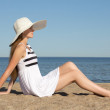 Pretty woman in striped dress and hat sitting on the beach — Stock Photo