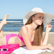 Beautiful teenager in pink bikini and white hat lying on the bea — Stock Photo