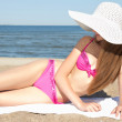 Beautiful woman in pink swimsuit lying on the beach — Stock Photo