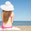 Rear view of young slim woman sitting on sandy beach — Stock Photo
