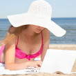 Young beautiful woman working on laptop at the beach — Stock Photo