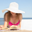 Woman with white laptop and book on the summer beach — Stock Photo