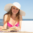 Female student with laptop and book on the beach — Stock Photo