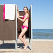 Beautiful woman in dressing cabin on the beach — Stock Photo #29188941