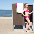 Slim beautiful woman in changing cabin on the beach — Stock Photo