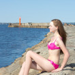 Beautiful model in pink bikini sitting on rocky beach — Stock Photo