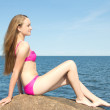 Beautiful slim model in pink bikini sitting on stone at rocky be — Stock Photo