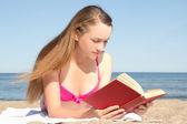 年轻女子在读本书在海滩上的粉色比基尼 — 图库照片