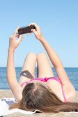 Woman photographing herself with mobile phone on the beach — Stock Photo