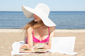 Female student with white laptop and book on the beach — Stock fotografie