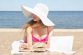 Vrouwelijke student met witte laptop en boek op het strand — Stockfoto