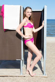 Slim beautiful woman in dressing cabin on the beach — Stockfoto