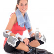 Young woman sitting with rollers on legs and bottle of water — Stock Photo