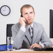 Bored businessman talking on phone in office — Stock Photo
