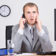 Frightened businessman talking on phone in office — Stock Photo