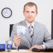 Business man showing money in bright office — Stok fotoğraf