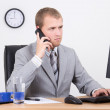Businessman talking on phone in office — Foto Stock