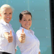 Portrait of two young attractive business women thumb up — Stock Photo