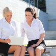 Two attractive business women sitting with laptop over street ba — Stock Photo