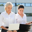 Two business women sitting with laptop and folder over street ba — Stock Photo