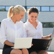 Two young business women sitting with laptop and folder over str — Stock Photo