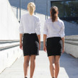 Rear view of two young attractive business women walking on stre — Stock Photo