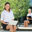 Attractive business women with folder and laptop sitting outside — Stock Photo
