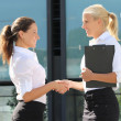 Stock Photo: Two beautiful business women shaking hands in street