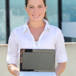 Attractive business woman showing laptop screen in the street — Stock Photo
