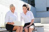 Laptop ile sokak ba oturan iki çekici kadın — Stok fotoğraf