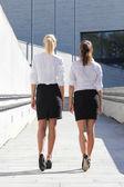 Bakifrån av två unga attraktiva företagskvinnor gå på stre — Stockfoto